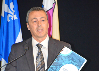 Laval's assistant city manager Clément Bilodeau is seen here holding a thick bound copy of the city's new master urban plan.
